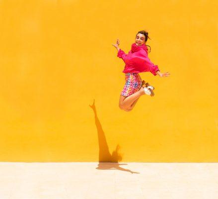 Chica-joven-alegre-salta-fondo-amarillo-por-HOTCREATIVIDAD
